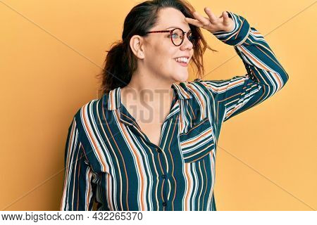 Young caucasian woman wearing casual clothes and glasses very happy and smiling looking far away with hand over head. searching concept.