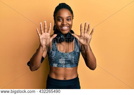 African american woman with braided hair wearing sportswear and arm band showing and pointing up with fingers number ten while smiling confident and happy.