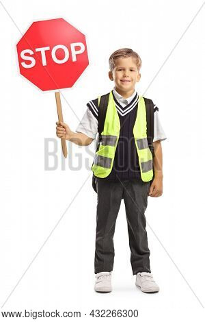 Little schoolboy with a safety vest and a stop traffic sign looking at camera and smiling isolated on white background