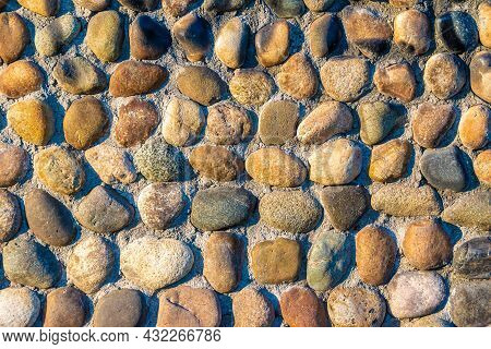 Multi-colored And Multi-textured Pebble Stones Lie In Rows Partially Pressed Into The Main Covering