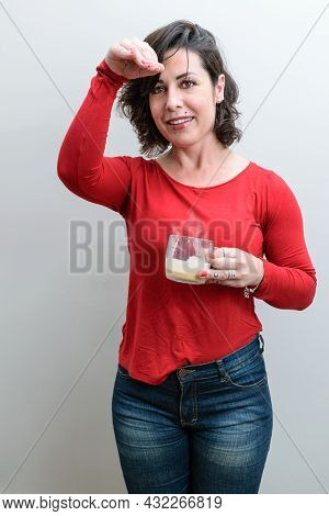 Brazilian, Holding A Mug Of Cappuccino, One Hand On Her Forehead And Telling A Story.