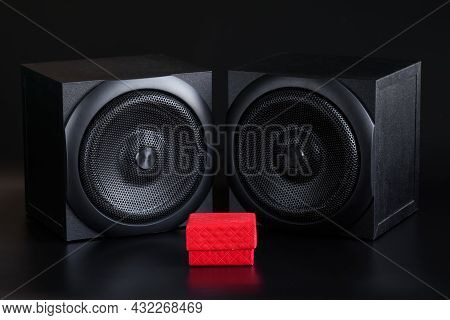 Red Gift Box And Two Single-way Audio Speakers On A Black Background. Hi-end Analog Acoustics Of A S