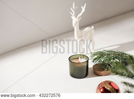Burning Christmas Candle And Toy Reindeer Next To Pine Branch And Red Christmas Ball. Copy Space For