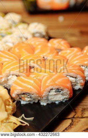 Hand Waiter Holding Set Delicious Fresh Sushi Slate Plate, Japanese Raw Fish In Traditional Restaura