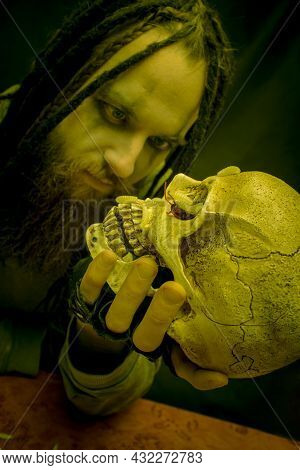 Maniac Posing With Skull Over Dark Background