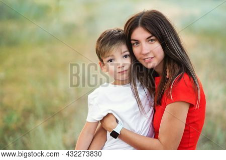 Affectionate Mom With Little Son Outdoor. Authentic Family Portrait. Mother And Child Embrace In Rur