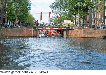 Amsterdam Netherlands - August 17 2017; Canal Cruise Boat Named Lovers, Passes Under Low Bridge With