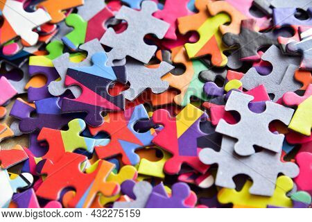 Closeup Heap Of Colorful Jigsaw Puzzle Game In A Box.