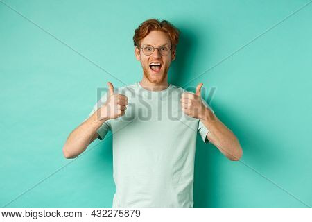 Excited Young Man With Red Hair, Wearing Glasses, Showing Thumbs-up And Agree Or Praise Something, S