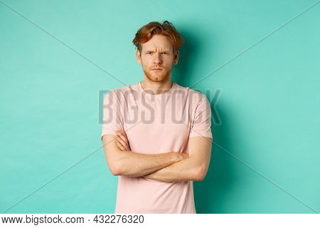 Young Man With Ginger Hair And Beard Looking Offended, Feeling Insulted And Staring At Camera, Sulki