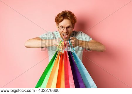 Excited Young Man, Shopper Holding Shopping Bags And Smiling Happy, Looking Excited At Purchased Ite
