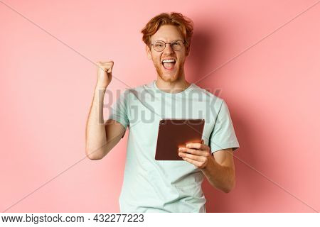 Image Of Happy Redhead Man Triumphing, Winning Online With Digital Tablet And Rejoicing, Standing Ov