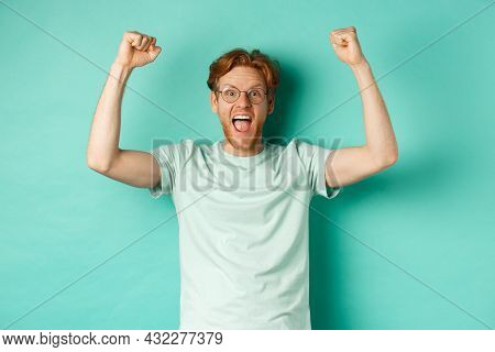 Young Redhead Man Feeling Like Champion, Raising Hands Up In Fist Pump Gesture And Shouting Yes With