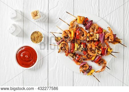 Grilled Shrimp Kabobs With Charred Red Onion, Sweet Pepper And Pineapple On A White Plate, Flat Lay