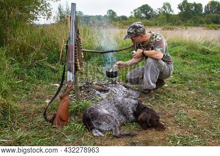 The Hunter Is In A Summer Field Camp. A Hunting Dog Is Lying In Front Of The Campfire. A Pot Hangs O