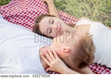 Young Couple Cuddling On A Picnic Blanket