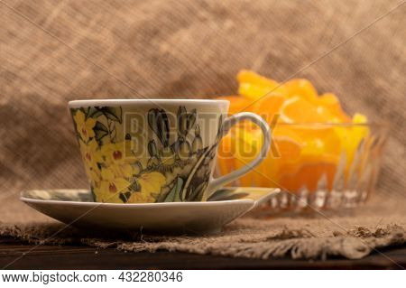 Multicolored Shaped Marmalade Lemon Slices In A Glass Vase And A Cup Of Tea On A Saucer, Close-up, S