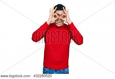 Handsome hispanic man wearing casual clothes and glasses doing ok gesture like binoculars sticking tongue out, eyes looking through fingers. crazy expression.