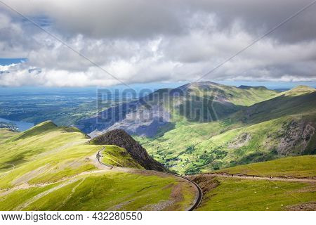 Railway track snaking up Mount Snowndon from Llanberis in the valley below. Snowdonia National Park, North Wales, UK, on a summer day. A popular tourist attraction for walking and hiking .