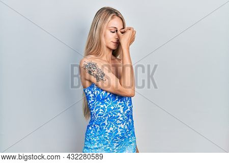 Young beautiful caucasian woman wearing summer dress tired rubbing nose and eyes feeling fatigue and headache. stress and frustration concept.