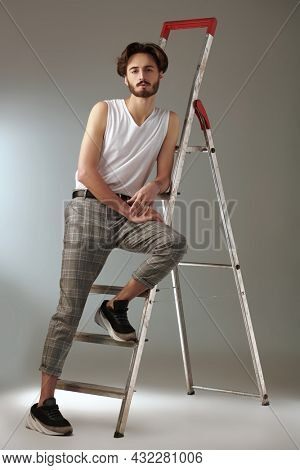 Men's fashion. Full length portrait of a handsome brunet man posing at studio in casual clothes by a ladder. Men's beauty and hairstyle.