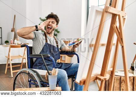 Young hispanic man sitting on wheelchair painting at art studio shouting and screaming loud to side with hand on mouth. communication concept.