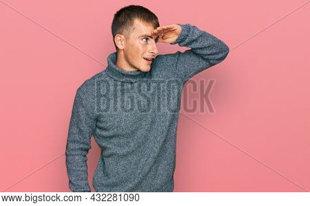 Young blond man wearing casual clothes very happy and smiling looking far away with hand over head. searching concept.