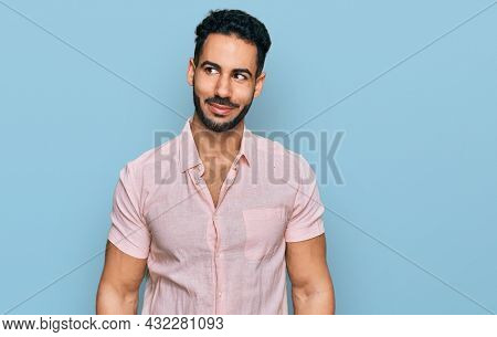 Hispanic man with beard wearing casual shirt smiling looking to the side and staring away thinking.