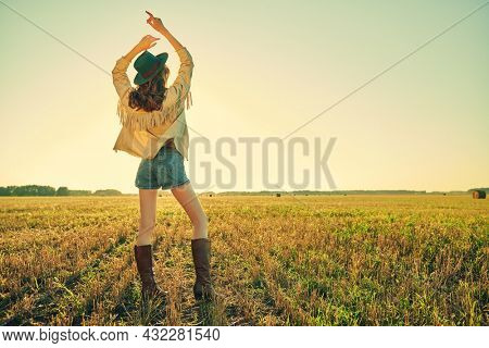 Romantic girl in western style clothes, hippie stands in the field and looks at the sunset. Fashion shot.