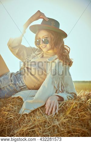 Modern hippie style. Beautiful girl in western style clothes, hippie lies on a haystack and smiles. Fashion shot.