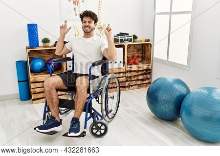 Hispanic man sitting on wheelchair at physiotherapy clinic gesturing finger crossed smiling with hope and eyes closed. luck and superstitious concept.
