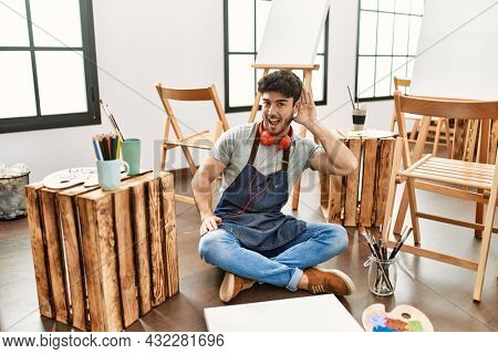 Young hispanic man sitting at art studio smiling with hand over ear listening an hearing to rumor or gossip. deafness concept.