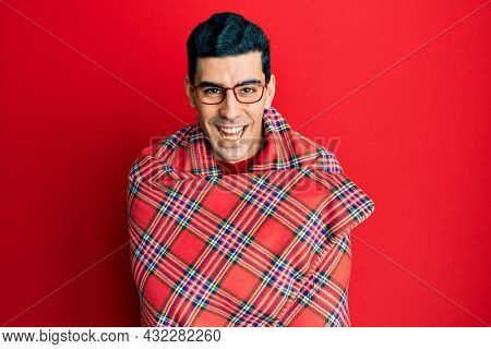 Handsome hispanic man wrapped in a red warm red blanket smiling and laughing hard out loud because funny crazy joke.