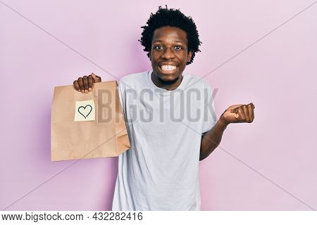 Young african american man holding take away paper bag with heart reminder screaming proud, celebrating victory and success very excited with raised arm