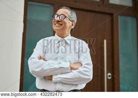 Middle age southeast asian man smiling confident with crossed arms by house entrance