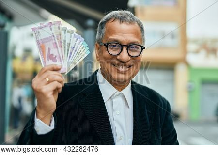 Middle age southeast asian man holding indian rupees banknotes at the city