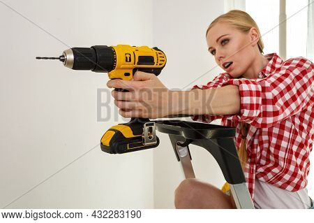 Young Determinated Woman Using Drill Doing Home Renovation. Female Construction Worker Having Drille