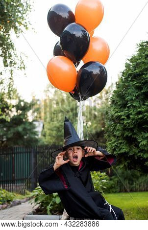 Playful Little Kid Boy In Carnival Costume Of Wizard Threatens Celebrating Halloween In Backyard