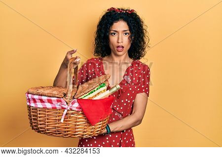 Young latin girl holding picnic wicker basket with bread in shock face, looking skeptical and sarcastic, surprised with open mouth