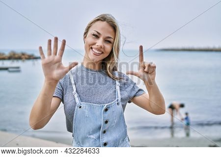 Young caucasian woman outdoors showing and pointing up with fingers number seven while smiling confident and happy.