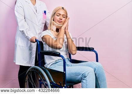Beautiful blonde woman sitting on wheelchair with collar neck sleeping tired dreaming and posing with hands together while smiling with closed eyes.