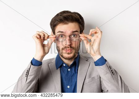 Close-up Of Handsome Man In Suit Trying Put On New Glasses, Standing On White Background