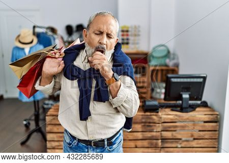 Handsome senior man holding shopping bags at boutique shop feeling unwell and coughing as symptom for cold or bronchitis. health care concept.