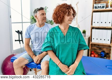 Physiotherapy woman working at pain recovery clinic with patient looking to side, relax profile pose with natural face with confident smile.