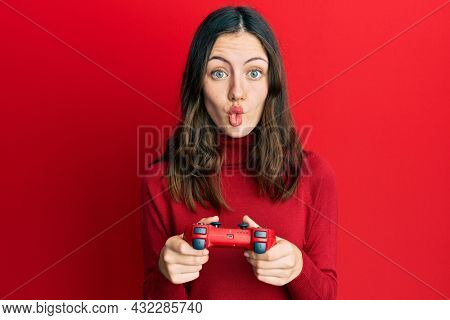 Young brunette woman playing video game holding controller making fish face with mouth and squinting eyes, crazy and comical.