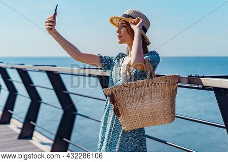 Beautiful Redhead Woman Posing At Sunny Day. Making Selfie Using Phone. Walks Along The Pier Near Th
