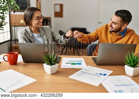 Two business workers hitting fists at the office.