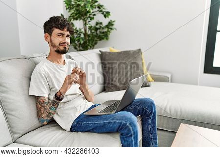 Hispanic man with beard sitting on the sofa disgusted expression, displeased and fearful doing disgust face because aversion reaction. with hands raised