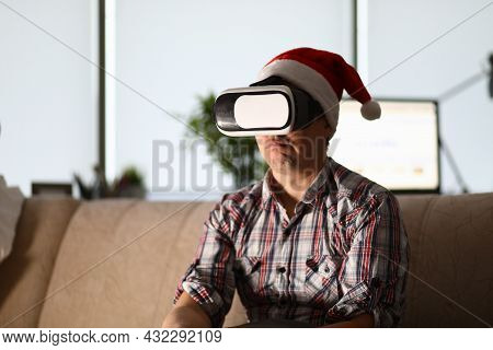 Man In Virtual Glasses Sits On Sofa Wearing Santa Claus Hat