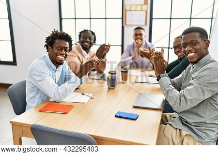 Group of african american business workers smiling and clapping looking to the camera at the office.